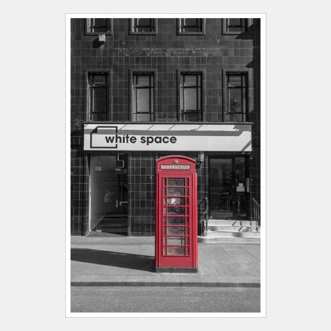 A Red Phone Booth in Front of the White Space Building, London